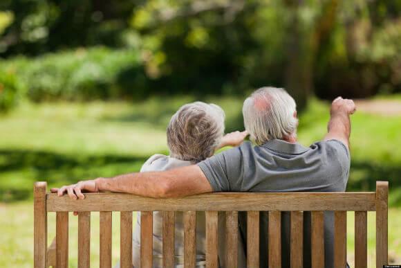 Casal de idosos sentado no banco apontando para o futuro e pensando na Aposentadoria por idade