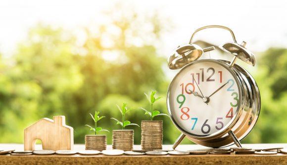 3 pilhas de moedas e um relógio para simbolizar a aposentadoria por tempo de contribuição.