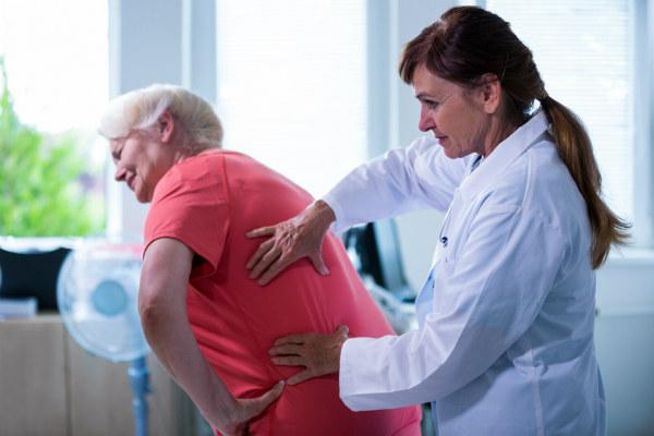 Paciente sendo examinada pela médica para ver se tem direito a aposentadoria por invalidez.